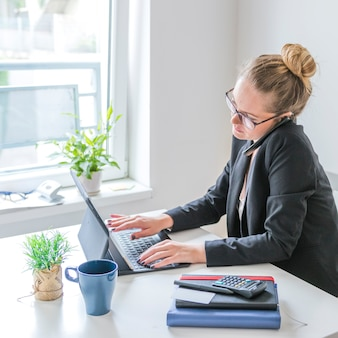 Businesswoman working on laptop using cellphone in office