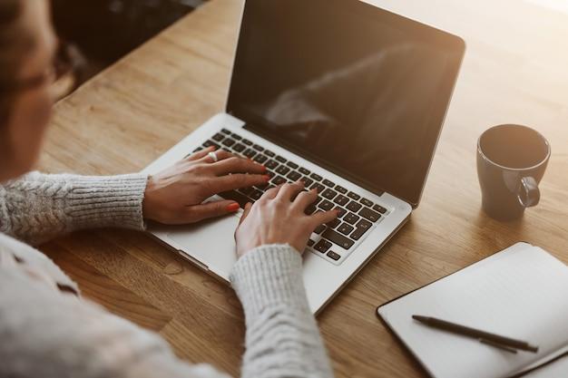 自宅に座ってラップトップ コンピューターで作業し、ホーム オフィス、クローズ アップを介して彼女のビジネスを管理する実業家