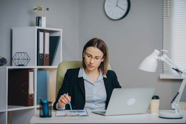 Деловая женщина, работающая над ноутбуком в ее современном офисе, держащем бумажный финансовый отчет.
