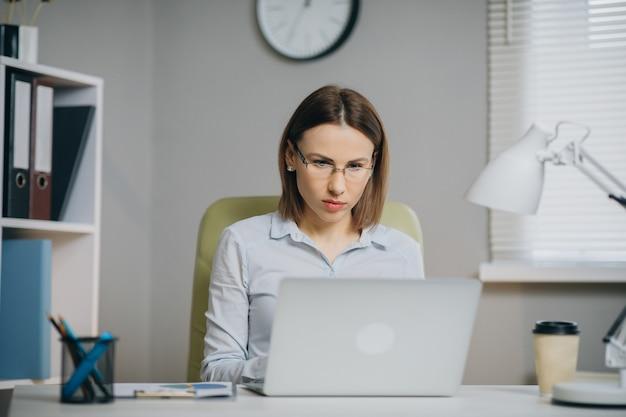 Предприниматель работает на ноутбуке в ее офисе. сильный независимый женский директор управляет деловой компанией