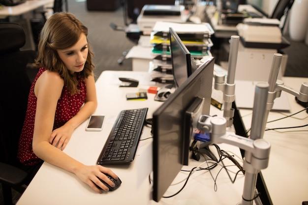 사무실 컴퓨터에서 작업하는 사업가