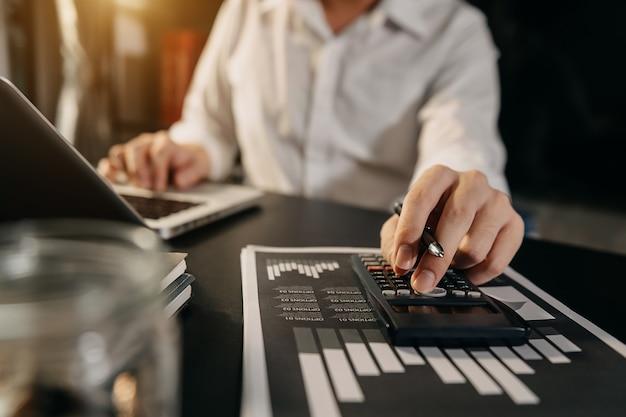 数値を計算するために計算機を使用してデスクオフィスで働く実業家、財務会計の概念