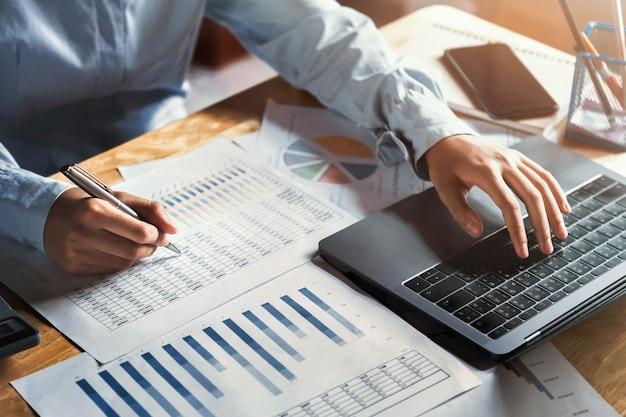 사무실에서 금융 확인 데이터에 노트북을 사용하는 책상에서 작업하는 사업가