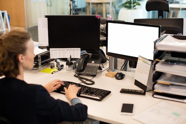 Деловая женщина, работающая на настольном пк в офисе