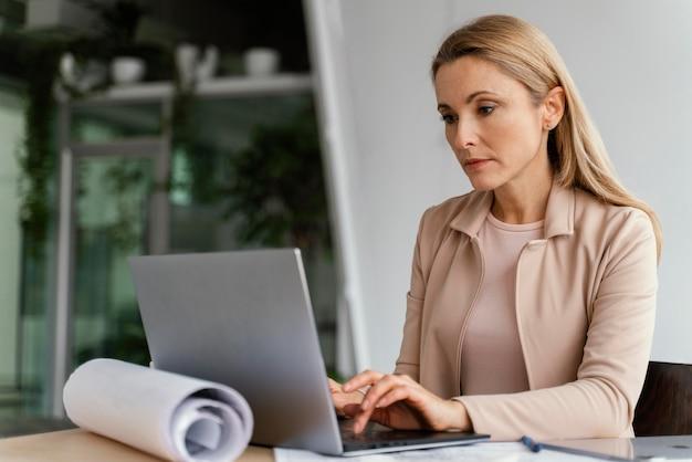 Деловая женщина, работающая на своем ноутбуке в офисе