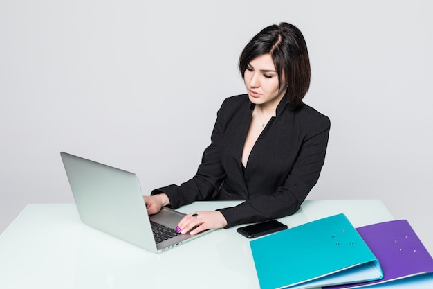 Деловая женщина, работающая на портативном компьютере за офисным столом