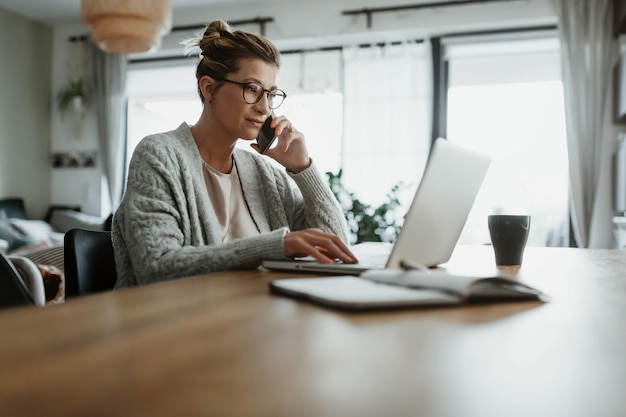 自宅に座って、ホーム オフィスを介して彼女のビジネスを管理するラップトップ コンピューターに取り組んでいる実業家