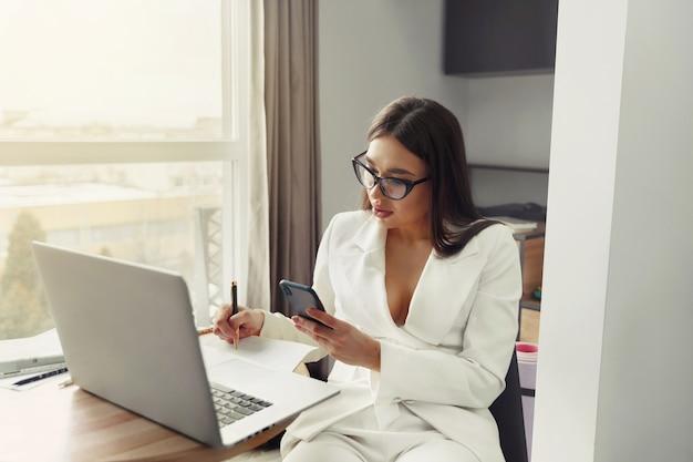 コロナウイルスまたはcovid-19検疫中にホームオフィスを介して彼女のビジネスを管理する自宅に座ってラップトップコンピューターで作業している実業家