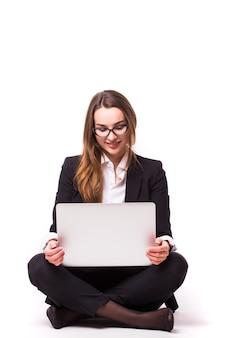 흰 벽에 고립 된 노트북에서 일하는 사업가
