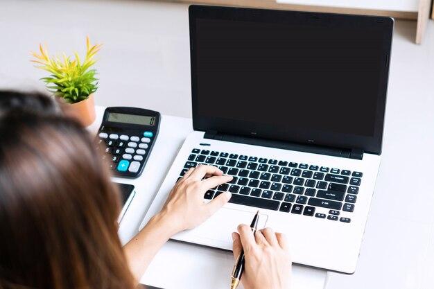 白いテーブルの上のコンピューターのラップトップでオンラインで作業する実業家