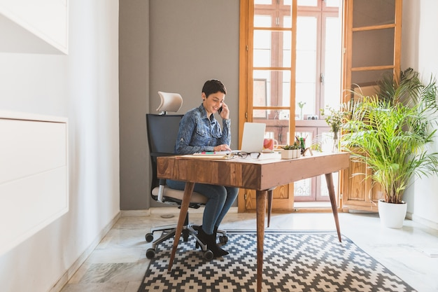 Businesswoman working while talking on the phone Free Photo