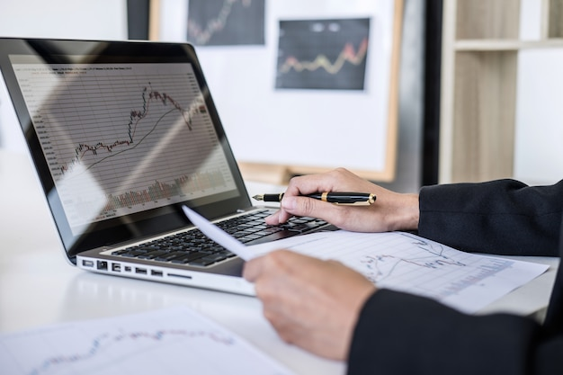 Businesswoman working with computer, laptop, discussing and analysis graph stock market trading
