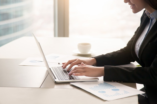 Коммерсантка работая с диаграммами на офисе используя компьтер-книжку, конец вверх