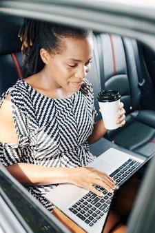 차에서 노트북으로 작업하는 사업가