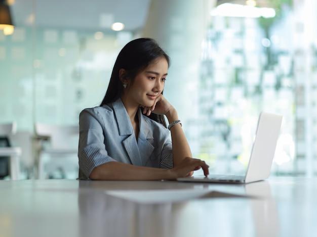 事務室のテーブルでノートパソコンで作業する実業家