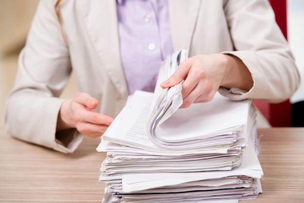 Businesswoman working with stack of papers