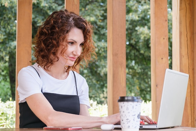 Businesswoman works at a laptop in a coworking space in a city park.