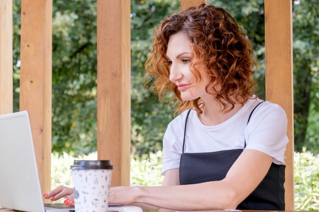 Businesswoman works at a laptop in a coworking space in a city park