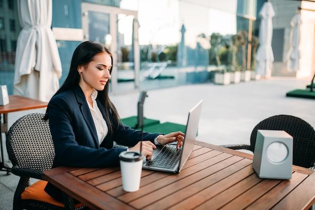 Деловая женщина работает на ноутбуке в офисе, вид сверху