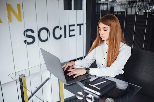 사업가 카페에서 노트북으로 작동합니다. 흰 블라우스와 검은 바지를 입은 젊은 여성이 테이블을 바라보고 있습니다.