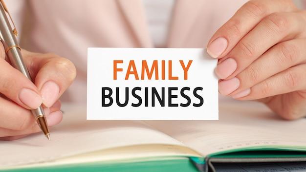実業家は、銀のペンとテキスト付きのハンドホールドカードを使用してノートに書き込みます:family business