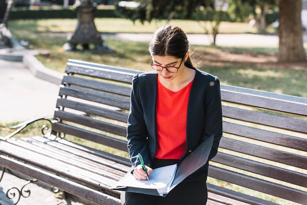 Businesswoman writing on bench