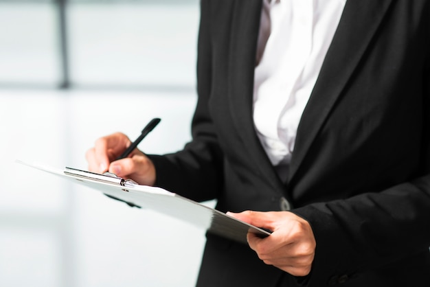 A businesswoman writing on clipboard with black pen