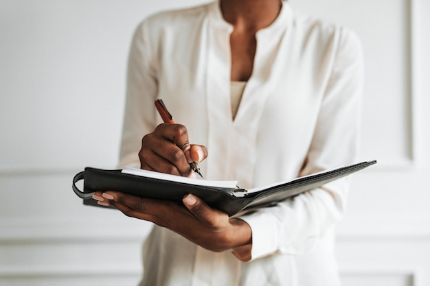 Businesswoman writing in a daily planner