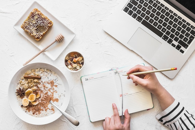 Businesswoman writing diary with pencil on workplace with laptop and healthy breakfast