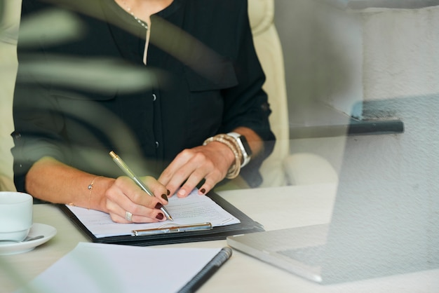 Businesswoman writing in document