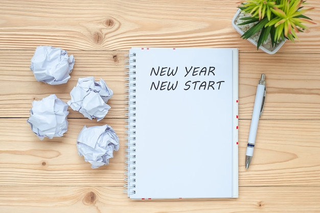 Businesswoman writing new year new start with notebook