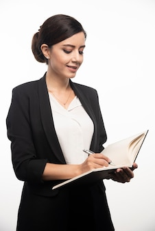 Businesswoman writing in notebook on white wall.