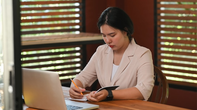 Businesswoman writing on notepad paper.