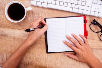 Businesswoman writing on diary on desk