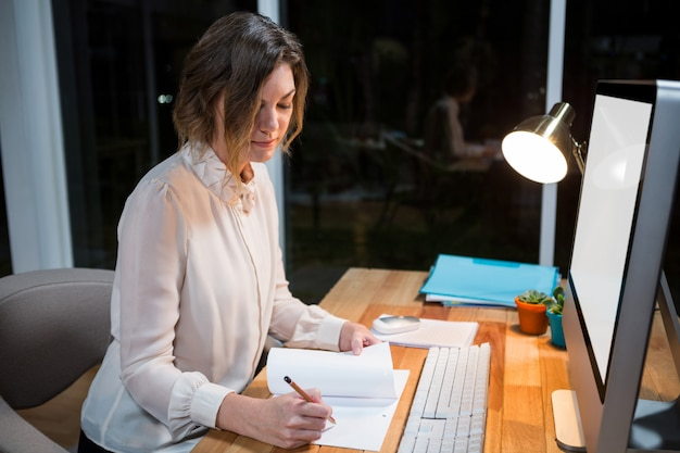 Businesswoman writing on paper at her desk