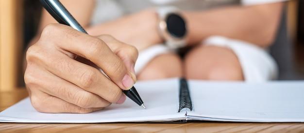 オフィスやカフェでノートに何かを書いている実業家、紙のレポートに署名とペンを持っている女性の手。ビジネスコンセプト