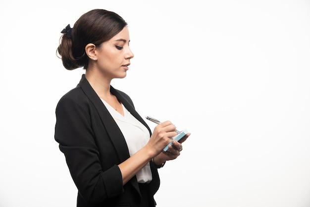 Imprenditrice iscritto in adesivo con una matita su sfondo bianco. foto di alta qualità