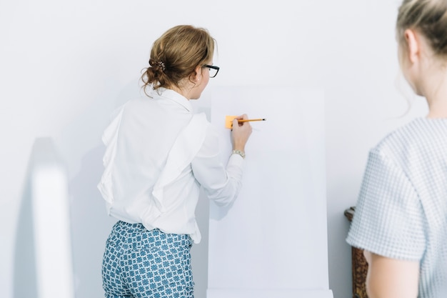Businesswoman writing on sticky notes with pencil over white board