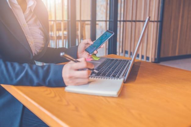 Деловые женщины пользуются мобильными телефонами, на экране отображаются таблицы анализа работы, и она делает заметки на бумаге с помощью черной ручки в офисе, переносного компьютера, установленного на деревянном столе в офисе.