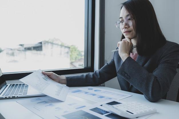 Бухгалтер бизнес-леди, держащая граф, использует калькулятор и ноутбук, делающий счет для уплаты налогов на белом столе в рабочем офисе.