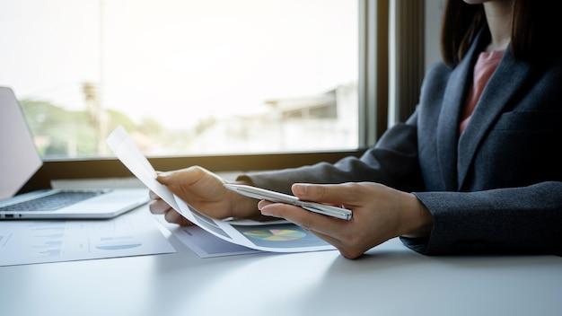 ビジネスウーマンの簿記係はペンを持って、ラップトップを使用して、作業オフィスの白い机に税金を支払うためのアカウントを使用します。