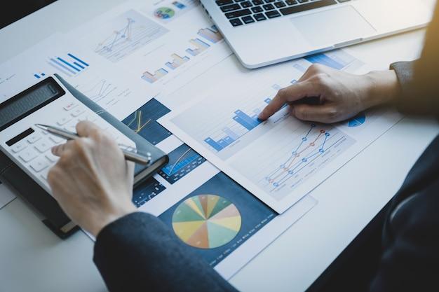 Рука бухгалтера-предпринимателя, указывающая на график, использует калькулятор и ноутбук на белом столе в рабочем офисе