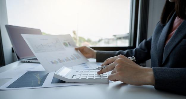 ビジネスウーマンの簿記係は、作業オフィスの白い机に税金を支払うためのアカウントを行う電卓とラップトップを使用します。