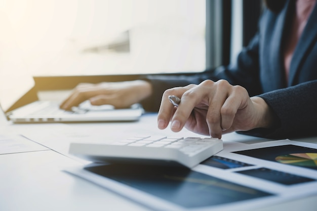 Деловые женщины-бухгалтеры рука используют калькулятор и ноутбук, делая счет для уплаты налогов на белом столе в рабочем офисе.