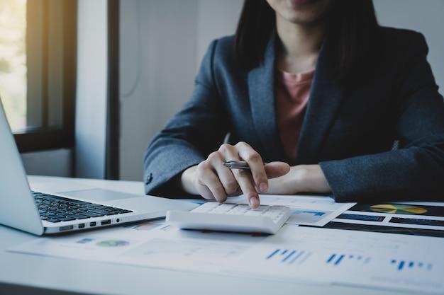Калькулятор и компьтер-книжка пользы руки бухгалтера предпринимателей на белом столе в рабочем офисе.
