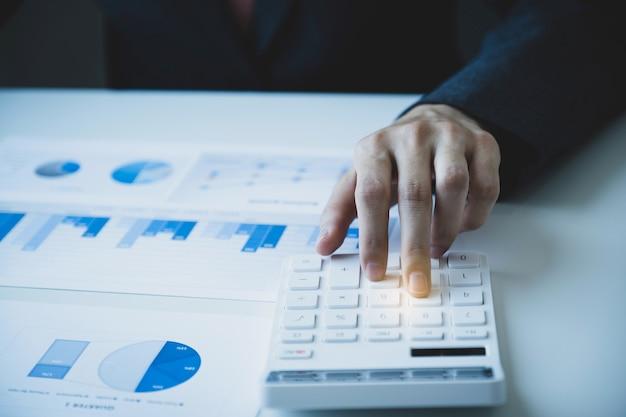Калькулятор использования руки бухгалтера-предпринимателя, делающий счет для уплаты налогов на белом столе в рабочем офисе.