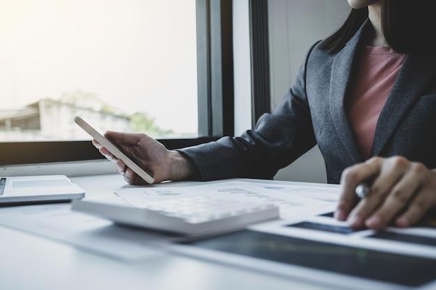 Бухгалтер бизнес-леди держит смартфон и использовать ноутбук на белом столе в рабочем офисе.