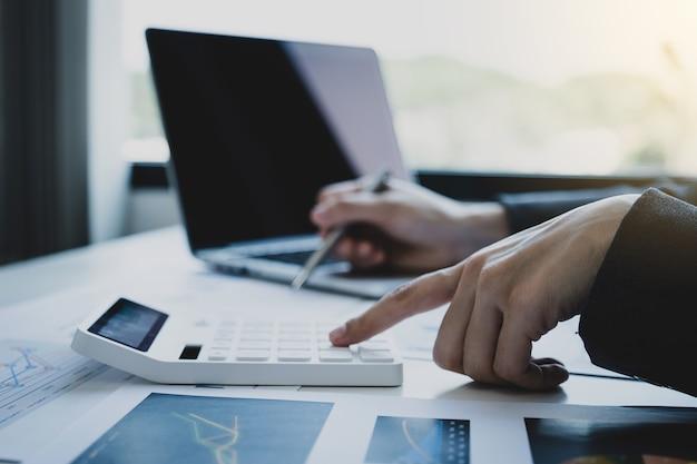 Бухгалтер бизнес-леди держит калькулятор и ноутбук на белом столе в рабочем офисе Premium Фотографии