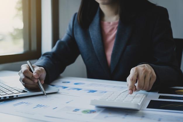 Бухгалтер бизнес-леди держит калькулятор использования ручки и ноутбук на белом столе в рабочем офисе.