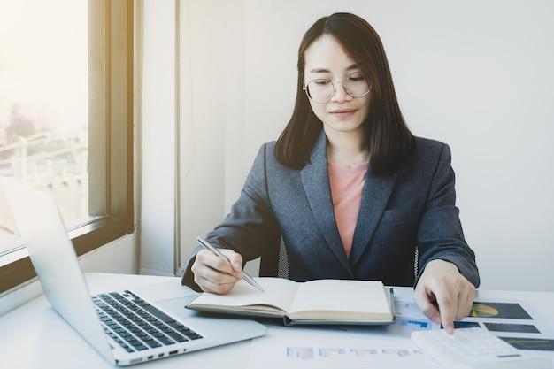 Бухгалтер бизнес-леди использует калькулятор и ноутбук, делая счет для уплаты налогов на белом столе в рабочем офисе.